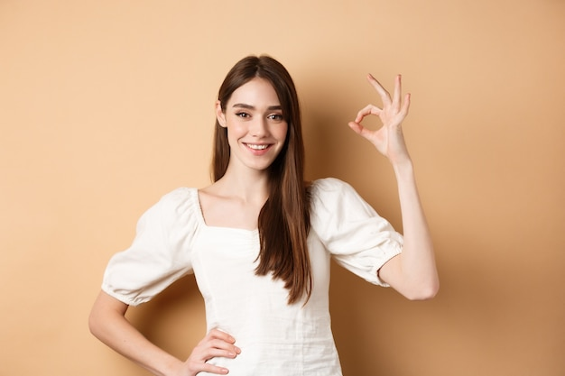 Molto bene. sorridente donna carina in camicetta bianca che mostra il segno giusto in approvazione, come e lode scelta eccellente, in piedi soddisfatta su sfondo beige.