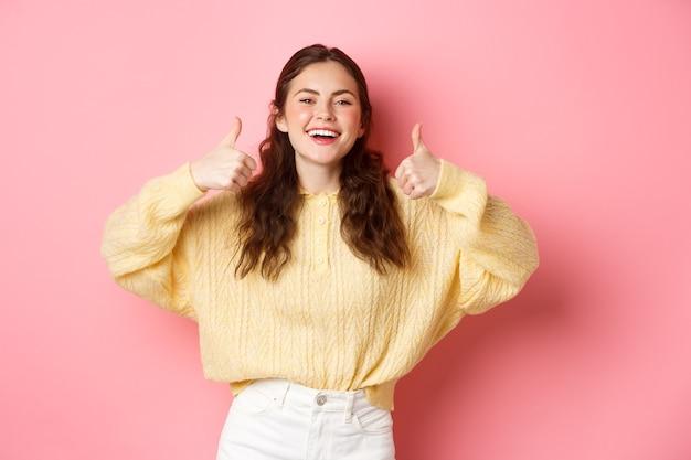 Molto bene, ben fatto. la ragazza sorridente è di supporto, ride e mostra i pollici in su in segno di approvazione, come un'idea fantastica, ti loda, in piedi contro il muro rosa