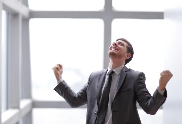 Uomo d'affari molto felice in piedi in officephoto con copia spazio