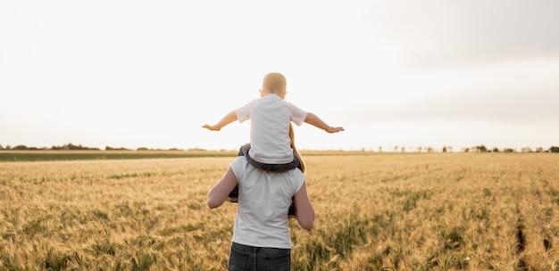Famiglia molto felice di madre e figlio che hanno divertimento all'aperto al tramonto estivo