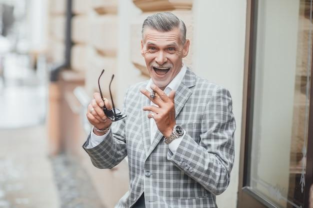 Anziano molto felice con gli occhiali da sole e la sigaretta costosa che sorride nella via