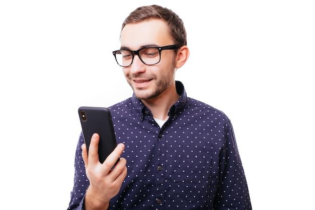 Giovane adulto sorridente molto felice in camicia bianca che esamina il suo telefono cellulare sul muro bianco white