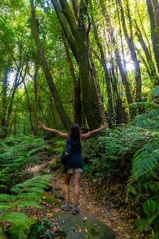 Una giovane donna molto felice che fa trekking, sul sentiero accanto alle felci