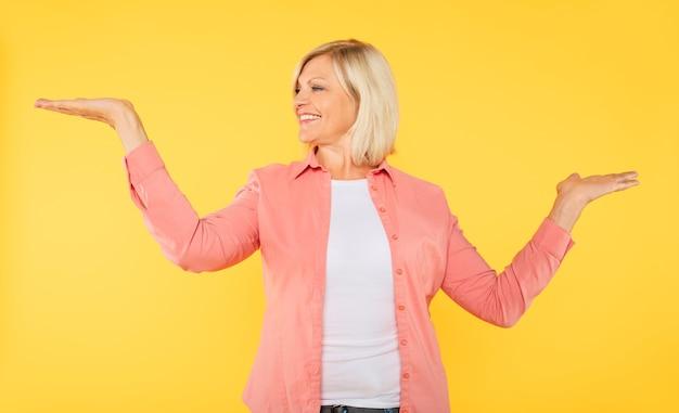 Decisione molto difficile. la bella donna anziana bionda carina in abbigliamento casual sta confrontando alcuni prodotti sui suoi palmi