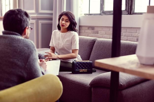 Molto utile. piacevole giovane donna seduta sul divano mentre ascolta i suoi consigli medici