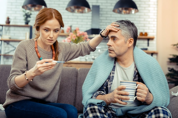 Temperatura molto alta. bella donna preoccupata che guarda il termometro elettronico mentre si preoccupa per suo marito