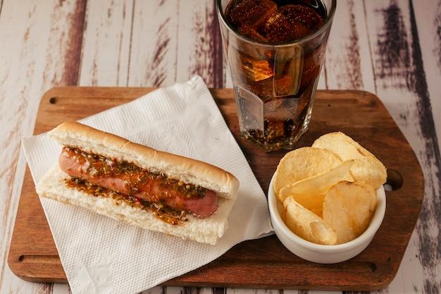 Vista molto alta di un hot dog con salsa chimichurri con soda e patatine su un tavolo rustico. vista orizzontale. concetto di cibo veloce e spazzatura.