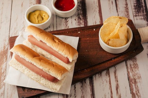 Vista molto alta di un paio di hotdog senza contorni con pentole di senape e ketchup e alcune patatine su un vassoio in legno rustico. vista verticale. concetto di cibo veloce e spazzatura.