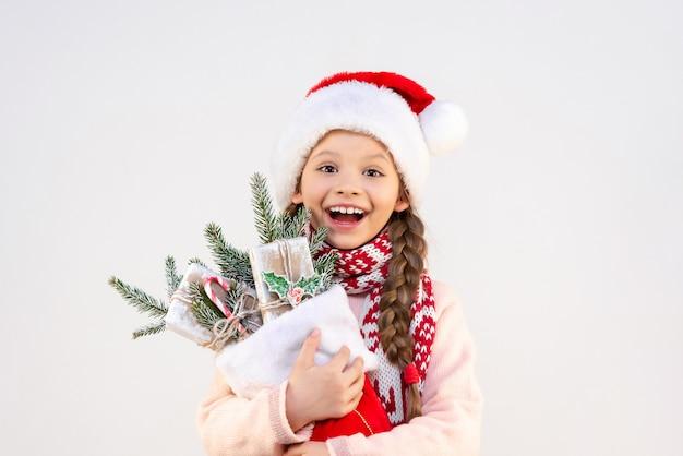 Una bambina molto gioiosa tiene in mano i regali e le decorazioni di capodanno.