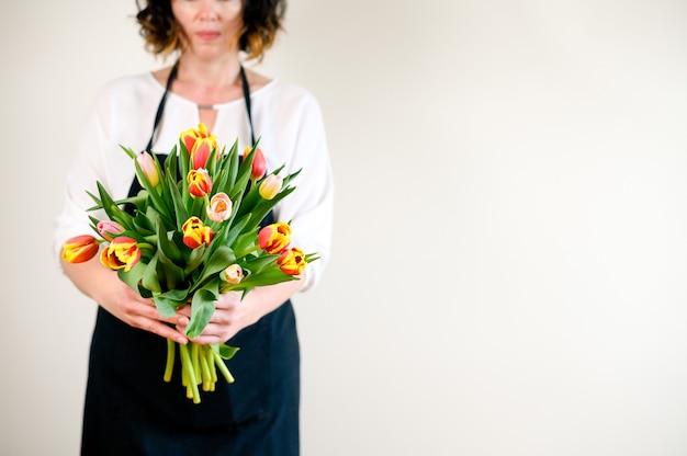 Donna fiorista molto bella che tiene un mazzo di bellissimi fiori sboccianti colorati di tulipani freschi sullo sfondo della parete.