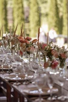 Un tavolo di nozze molto ben decorato con un bellissimo arredamento con piatti e tovaglioli nel giardino primaverile. bellissimi fiori sul tavolo nel giorno del matrimonio. la tavola elegante. giorno del matrimonio
