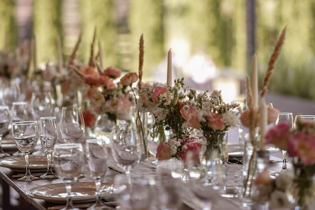 Un tavolo di nozze molto ben decorato con un bellissimo arredamento con piatti e tovaglioli nel giardino primaverile. bellissimi fiori sul tavolo nel giorno del matrimonio. la tavola elegante.