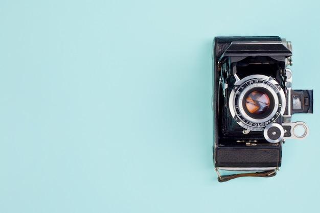 Macchina fotografica molto vecchia su uno sfondo blu delicato. vista dall'alto.