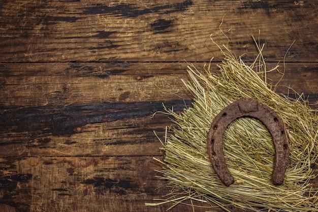 Cavallo di ferro di cavallo in ghisa molto vecchio su fieno. simbolo di buona fortuna, concetto di san patrizio. fondo in legno antico, accessori per cavalli