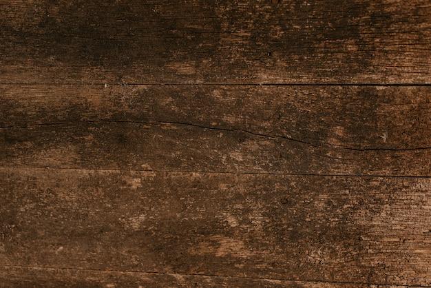 Sfondo di assi di legno marrone scuro squallido molto vecchio con crepe, graffi e macchie