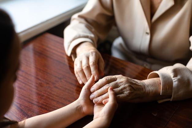 Donna molto anziana che tiene le mani di un bambino
