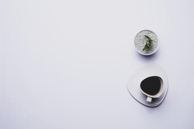 Una tazza di caffè moderna molto semplice su uno sfondo bianco e una pianta verde tema minimalista