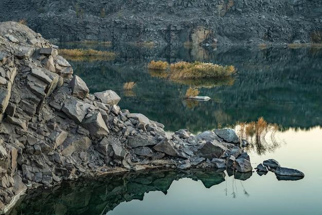 Un bellissimo lago molto piccolo circondato da grandi cumuli di rifiuti di pietra dal duro lavoro nella miniera