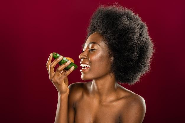 Molto saporito. felice donna allegra guardando l'avocado mentre si prepara a mangiarlo