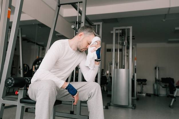 Molto stanco dopo un intenso allenamento, un uomo si siede in palestra asciugandosi il sudore dal viso con un asciugamano. prendersi cura del proprio corpo