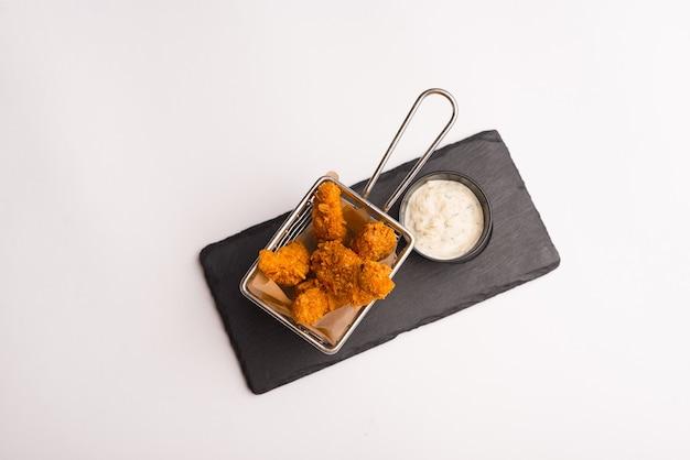 Vista dall'alto di un cesto pieno di dita fritte o pepite su sfondo bianco.
