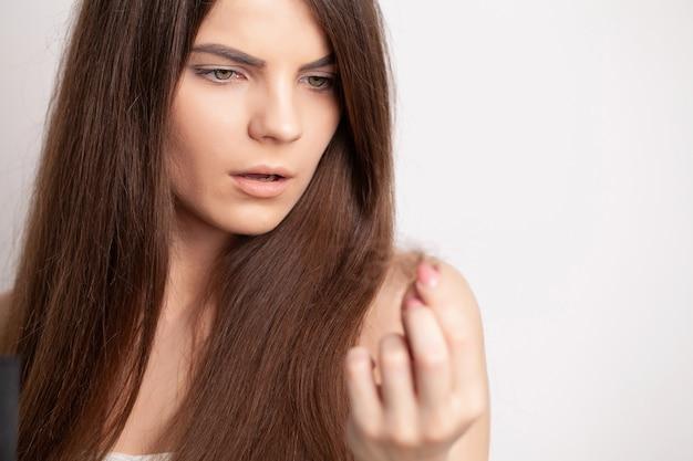 Una giovane donna molto arrabbiata ha un problema con la caduta dei capelli