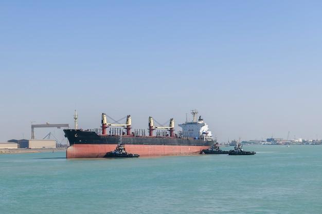 Nave in avvicinamento all'attracco con assistenza ai rimorchiatori. operazioni di ormeggio. bulker. nave da carico a secco.