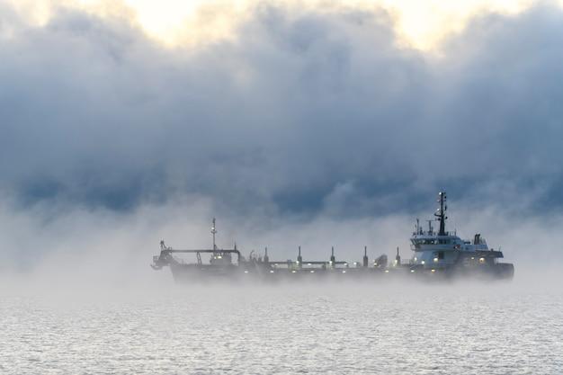 Nave impegnata nel dragaggio draga al lavoro in mare forte nebbia nel mare artico
