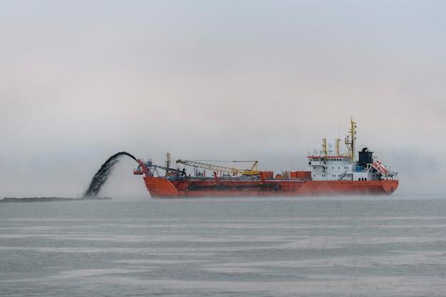 Nave impegnata nel dragaggio all'ora del tramonto. draga della tramoggia che lavora in mare. nave materiale di scavo da un ambiente acquatico.