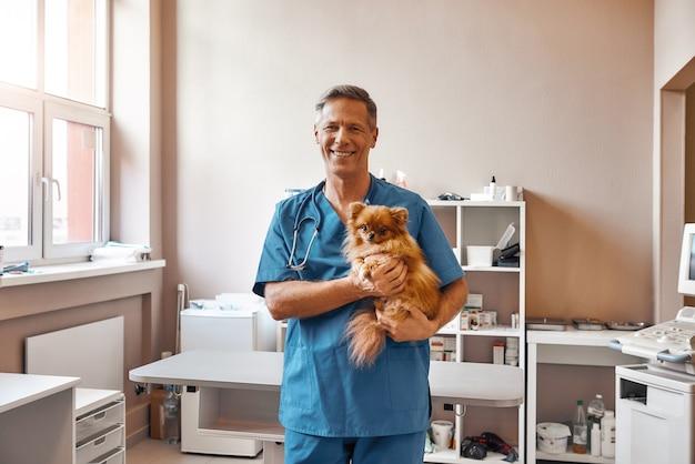 Il veterinario in uniforme da lavoro tiene in mano un cagnolino e sorride alla telecamera mentre si trova in una clinica veterinaria