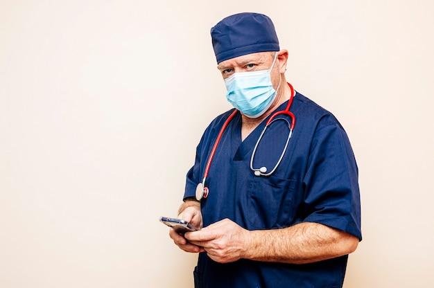 Medico veterano utilizzando smart phone con parete beige