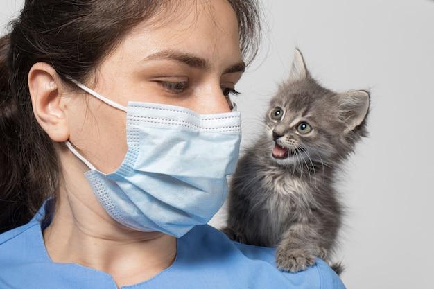Un veterinario in maschera protettiva e uniforme e un piccolo gattino grigio.