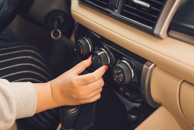 Vmano di donna che accende il sistema di climatizzazione dell'auto, pulsante sul cruscotto nel pannello dell'auto