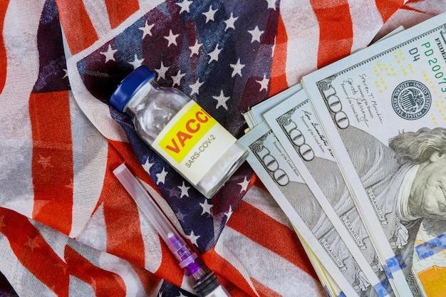 Fiale bottiglia di vetro di vaccino americano sars-cov-2, covid-19 coronavirus con molti dollari di fatture usa la bandiera usa sullo sfondo