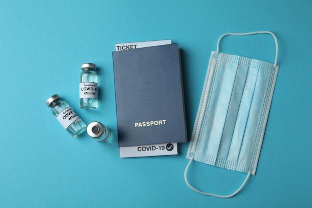 Fiale con vaccino covid - 19, mascherina medica e passaporto sul tavolo blu