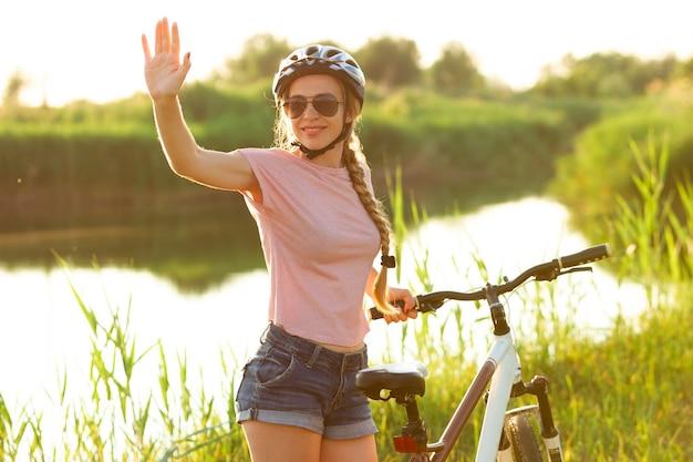 Vibrazioni. gioiosa giovane donna in sella a una bicicletta presso la passeggiata lungo il fiume e il prato.