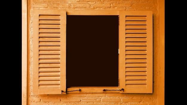 Finestra di legno color arancio vibrante dell'albicocca con le persiane di apertura sul muro di mattoni