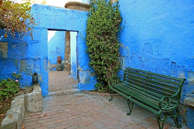 Vibrante colore blu muro di pietra e panchina verde all'interno del monastero di santa catalina arequipa perù