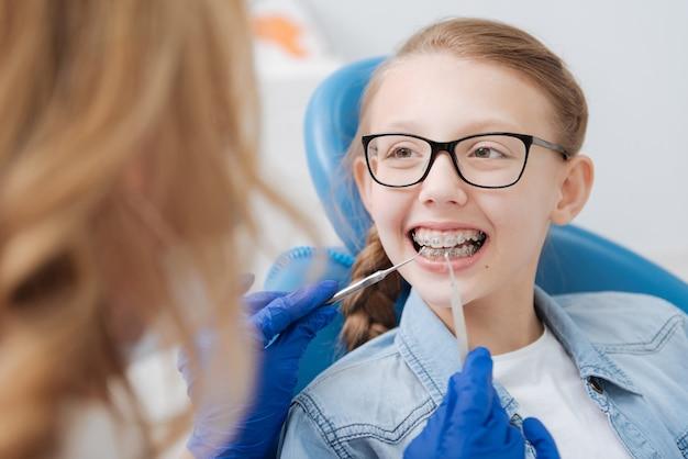 Vibrante brillante ragazza intelligente che paga al dentista una visita regolare per mantenere uno strumento speciale nella sua falena e assicurarsi che tutto funzioni correttamente