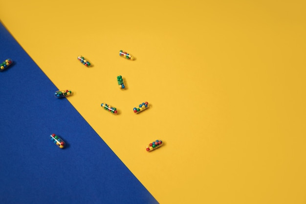 Lay piatto colorato vibrante di capsule di pillole medicinali riempite con granelli di zucchero candito su sfondo giallo e blu. concetto creativo di uso della medicina per overdose e dipendenza da integratore alimentare.