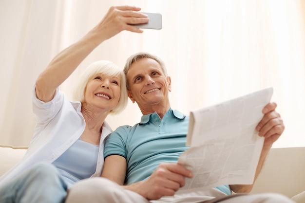 Vivace donna vivace creativa che utilizza la parte anteriore anteriore per fare una foto mentre memorizza una bella mattinata con suo marito