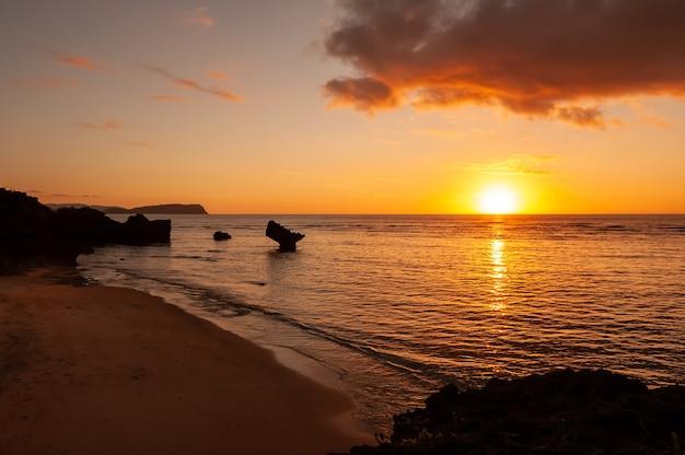 Tramonto vibrante con colori arancioni e gialli e alcune rocce tipiche dell'isola di iriomote di okinawa seashore