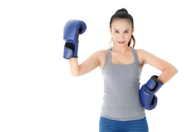 Giovane combattente asiatica vittoriosa in guanti da boxe blu alzando la mano e sorridendo felicemente mentre celebrava il trionfo su sfondo bianco