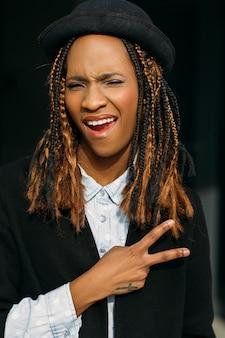 Gesto di vittoria. gioiosa giovane donna nera. felice donna afroamericana, modello elegante in posa su sfondo scuro, concetto di felicità