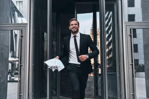 Vittoria! bel giovane uomo d'affari in abito completo che sorride e tiene in mano un documento mentre si cammina all'aperto
