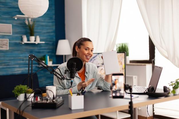 Video blogger che registra talk show in podcast di home studio utilizzando attrezzature moderne. vlogger influencer creatore di contenuti creativi che realizza serie online con omaggi per il pubblico.
