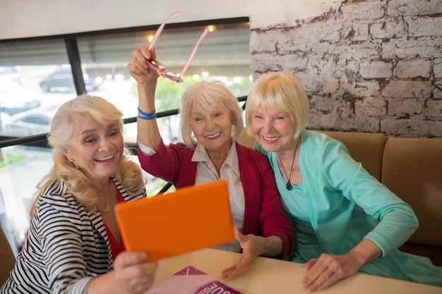 Video chiamata. donne anziane di bell'aspetto che fanno una videochiamata e sembrano eccitate