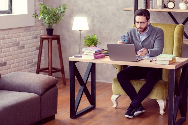 Video chiamata. simpatico indovino esperto che guarda lo schermo del laptop mentre fa una videochiamata con il suo cliente