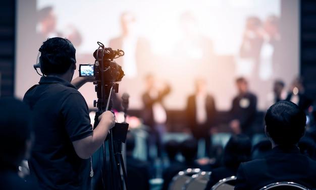 Operatore di videocamera che lavora con la sua attrezzatura all'evento al coperto