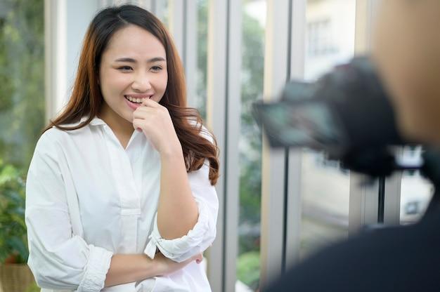 Una videocamera di registrazione di fiduciosa bella imprenditrice intervistata, dietro il concetto di scena,